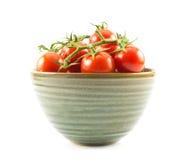 Vermelho, pouco, tomates de cereja em um copo verde em um fundo branco Imagens de Stock Royalty Free