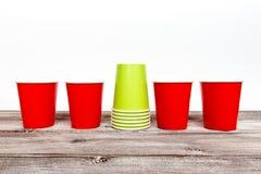 Vermelho quatro e pilha de copos descartáveis de papel verdes para o café e de bebidas não alcoólicas no fundo de madeira imagens de stock royalty free