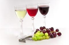Vermelho, rosa e vinhos brancos com uvas. Imagem de Stock
