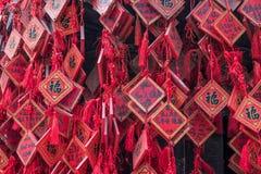 Vermelho tradicional que deseja envelopes com desejo escrito à mão Placa vermelha do cartão que pendura em desejar a árvore Imagem de Stock