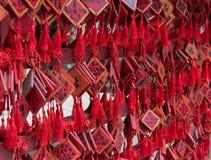 Vermelho tradicional que deseja envelopes com desejo escrito à mão Placa vermelha do cartão que pendura em desejar a árvore Fotos de Stock