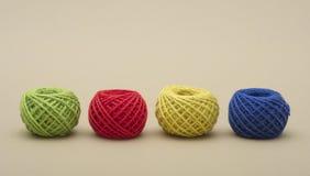 Vermelho, verde, amarelo, o azul rosqueia no fundo escuro Fotografia de Stock Royalty Free