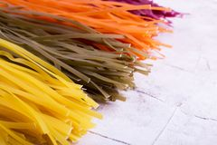 Vermicelli of four colorful flowers. Long colored pasta, space for text. Not cooked pasta stock photos