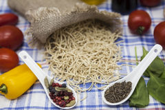Vermicelli Italian pasta set for the creation : cherry tomatoes, olive oil, balsamic sauce, garlic, spices, sea salt, salad on a r Stock Images