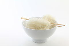Vermicelli Noodles in White Bowl. Dried vermicelli (angel's hair) noodles in white bowl with chopsticks. On white background stock images