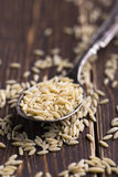 Vermicelli pieces in a spoon on a wooden background Royalty Free Stock Image