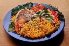 Vermicelli, tagliatelle con la bistecca della carne di maiale su un piatto blu, decorato con i pomodori affettati immagini stock libere da diritti