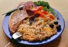 Vermicellis, nouilles avec le bifteck de porc d'un plat bleu avec une fourchette, décorée des tomates coupées en tranches image stock