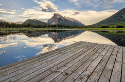 Vermilion Lakes Dock Side. Wooden dock beside Vermilion lakes with perfect mountain reflection Stock Image