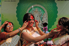 Vermilion Play. Bengali women apply vermilion on each other while playing Sindoor Khela (vermilion game) on the last day of Durga Puja Stock Photo