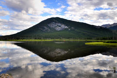 Vermillion Lake reflection. Typical Canadian outdoor lake scenery with clouds and mountains reflected on clear water Stock Photos
