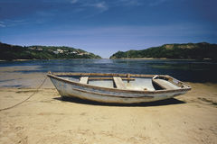 Verminderung Rowboat auf Strand Stockbild