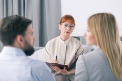 Vermittler, der mit einem Paar während einer Sitzung spricht stockbild