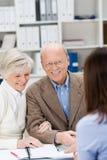 Vermittler, der zu einem lächelnden älteren Paar plaudert Stockfotos