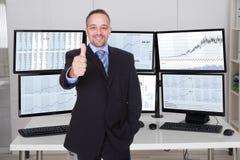 Vermittler Gesturing Thumbs Up gegen mehrfache Monitoren Stockbild