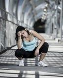 Vermoeid en uitgeputte sportvrouw ademhaling en het koelen neer na het lopen royalty-vrije stock afbeeldingen