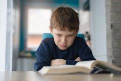 Vermoeid 8 jaar oude jongens die zijn thuiswerk doen bij de lijst Royalty-vrije Stock Afbeeldingen