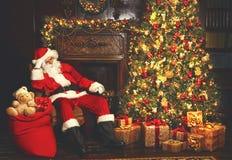 Vermoeid kerstman in slaap als voorzitter dichtbij Kerstboom stock afbeeldingen