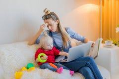 Vermoeid mamma die aan computer proberen te werken stock afbeelding