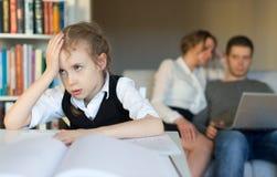 Vermoeid meisje dat thuiswerk doet Stock Foto