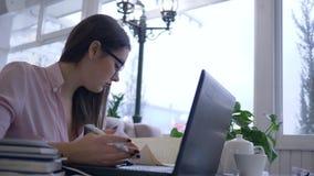 Vermoeid overwerkt studentenwijfje die in oogglazen met laptop computer met online les tijdens afstand bestuderen stock video