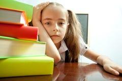 Vermoeid schoolmeisje achter stapel boeken stock foto