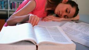 Vermoeid schoolmeisje die op bureau in bibliotheek leunen stock videobeelden