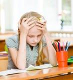 Vermoeid schoolmeisje in klaslokaal Stock Afbeeldingen