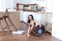 Vermoeid sexy meisje in de keukenzitting op de vloer Stock Foto