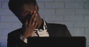 Vermoeid van het werken aan computer verhoogt de jonge zwarte man zijn glazen en wrijft zijn ogen Werkverslaafde, die hard werken stock footage