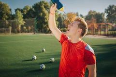 Vermoeid voetbalster gietend water op gezicht Hij krimpt Jonge mensentribune op gazon Vier ballen zijn achter hem stock foto's