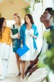 vermoeide Afrikaanse Amerikaanse studentenzitting op vensterbank terwijl groep studentenmeisjes die door universiteitsgang lopen royalty-vrije stock afbeeldingen
