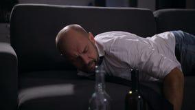 Vermoeide alcoholistontwaken op de laag met kater stock videobeelden