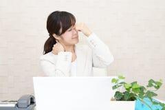 Vermoeide Aziatische bedrijfsvrouw royalty-vrije stock afbeelding