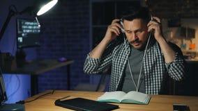 Vermoeide beambte die lamp en laptop uitzetten en werkplaats verlaten bij nacht stock footage