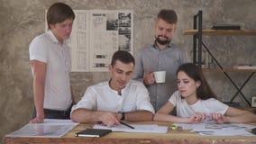 Vermoeide beambten die aan een tekening, een kop werken van koffie in de handen van een mens stock videobeelden