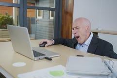Vermoeide bedrijfsmens bij zijn bureau Stock Foto
