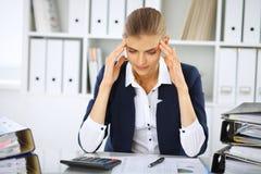 Vermoeide bedrijfsvrouw of vrouwelijke accountant met rekeningen en document omslagen in bureau stock fotografie