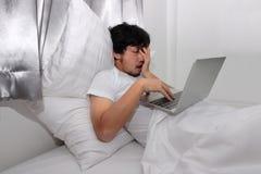 Vermoeide beklemtoonde jonge Aziatische mens die slaperig terwijl het gebruiken van laptop op het bed in slaapkamer voelen Het Co royalty-vrije stock fotografie