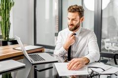 Vermoeide belastingsmanager die op het kantoor werken stock foto