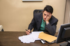 Vermoeide bored jonge zakenmanzitting in bureau Royalty-vrije Stock Foto's