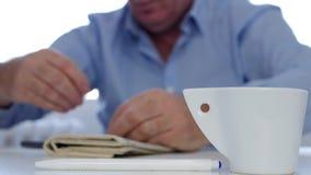 Vermoeide Businessperson Napping met een Koffie en een Krant op de Lijst stock videobeelden