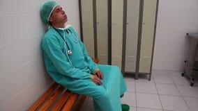 Vermoeide chirurgenzitting op een bank stock videobeelden