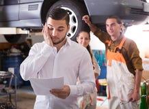 Vermoeide cliënt bij de autodienst stock afbeeldingen