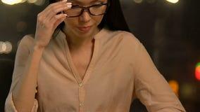Vermoeide dame die glazen opstijgen en neusbrug wrijven, die aan gebrek aan energie lijden stock footage