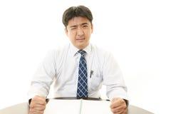 Vermoeide en beklemtoonde Aziatische zakenman royalty-vrije stock afbeelding