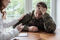 Vermoeide en droevige militair met oorlogssyndroom tijdens therapie met psychotherapist stock afbeelding