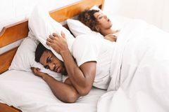 Vermoeide en geërgerde mens van zijn meisje het snurken stock foto