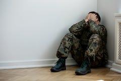 Vermoeide en gedeprimeerde militair met oorlogssyndroom alleen thuis Exemplaarruimte op de muur royalty-vrije stock foto's