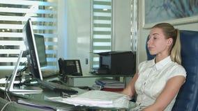 Vermoeide en slaperige jonge bedrijfsvrouw bij het bureau met laptop stock videobeelden